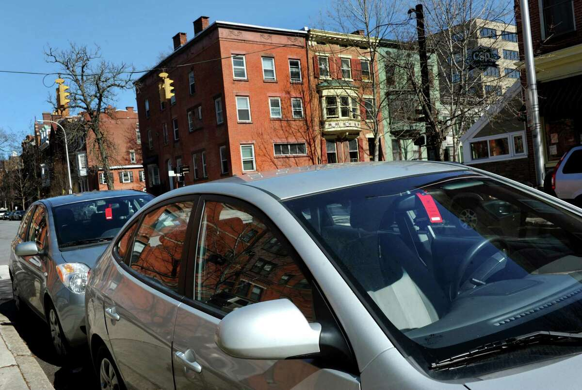 Red visitor parking tags hang on the rear view mirror of two cars parked in a row in Center Square on Wednesday, April 17, 2013, in Albany, N.Y. (Cindy Schultz / Times Union)