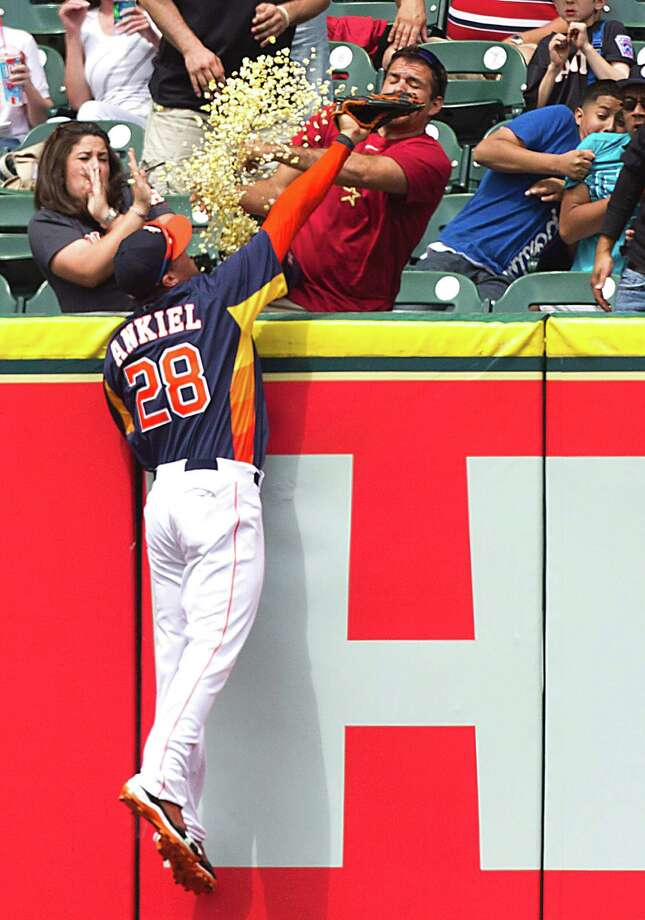 Talk about a drop in the bucket. With Astros right fielder Rick Ankiel unable to rob the Indians' Drew Stubbs of a sixth-inning home run on Sunday, one fan finds himself the proud owner of a popcorn ball. Photo: Brett Coomer, Staff / © 2013 Houston Chronicle