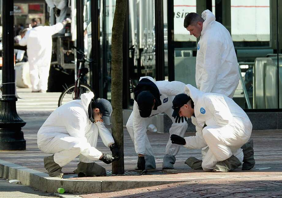 Investigators work near the finish line of the Boston Marathon as part of the investigation into last week's bombings, which includes determining if terror groups were involved. Photo: Kevork Djansezian / Getty Images