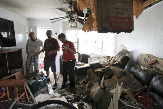 Scott Tacker (second from left) and wife Jennifer get help from her brother Will Matus as they retrieve belongings from their damaged West home.
