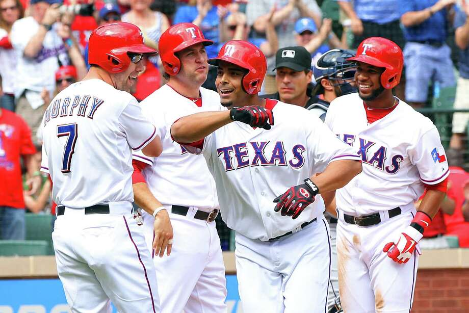 Nelson Cruz of the Rangers (center) is congratulated by (from left) David Murphy, Lance Berkman and Elvis Andrus after bringing them home with his fifth-inning grand slam. Photo: Rick Yeatts / Getty Images