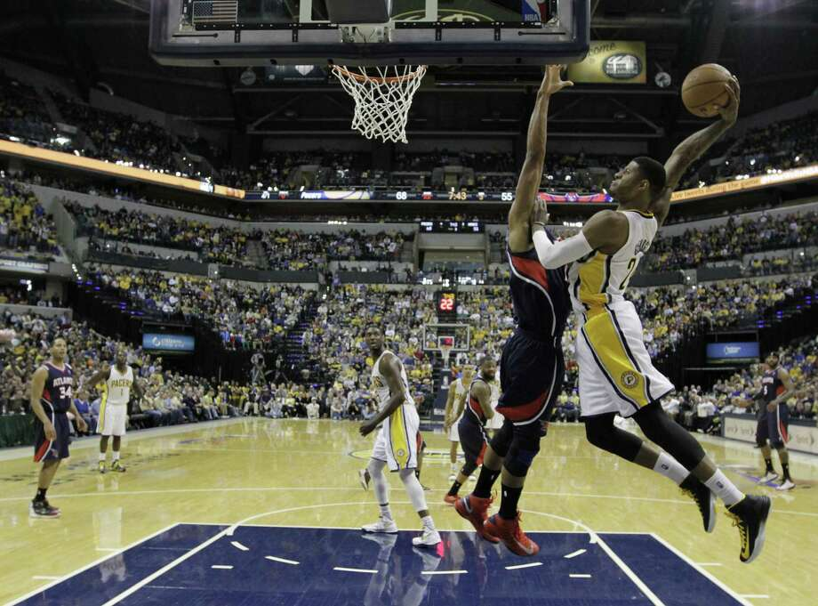 The Pacers' Paul George (right) goes up for a dunk against the Hawks' Al Horford. George led Indiana with 23 points, 11 rebounds and 12 assists. Photo: Darron Cummings / Associated Press