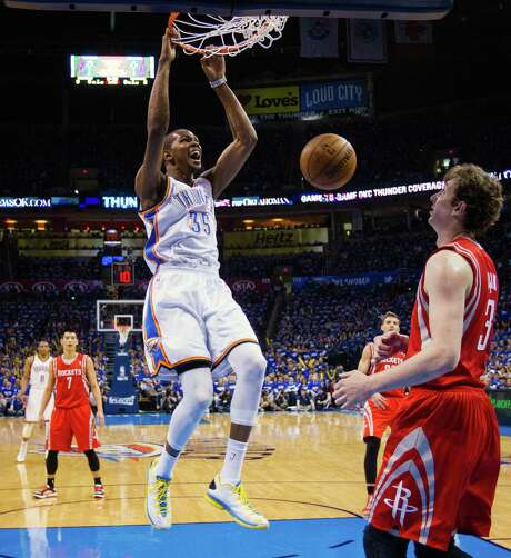 Thunder forward Kevin Durant, who had 24 points and this monster dunk in front of Omer Asik (3) on Sunday night, is a tough assignment for the Rockets. Photo: Smiley N. Pool, Staff / © 2013  Houston Chronicle