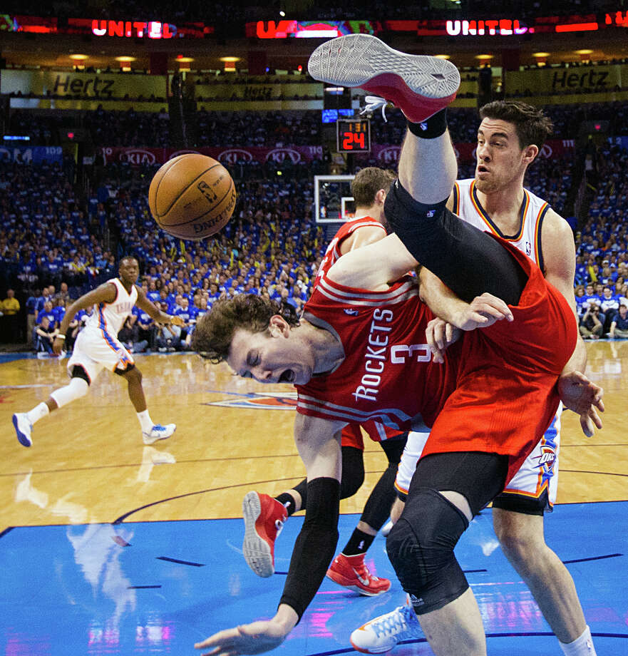 Oklahoma City's Nick Collison gives Rockets center Omer Asik (3) a rough welcome to the first round of the playoffs on Sunday night. The Thunder battered the Rockets all night and led by as many as 33 before settling for a 120-91 blowout win. Photo: Smiley N. Pool, Staff / © 2013  Houston Chronicle