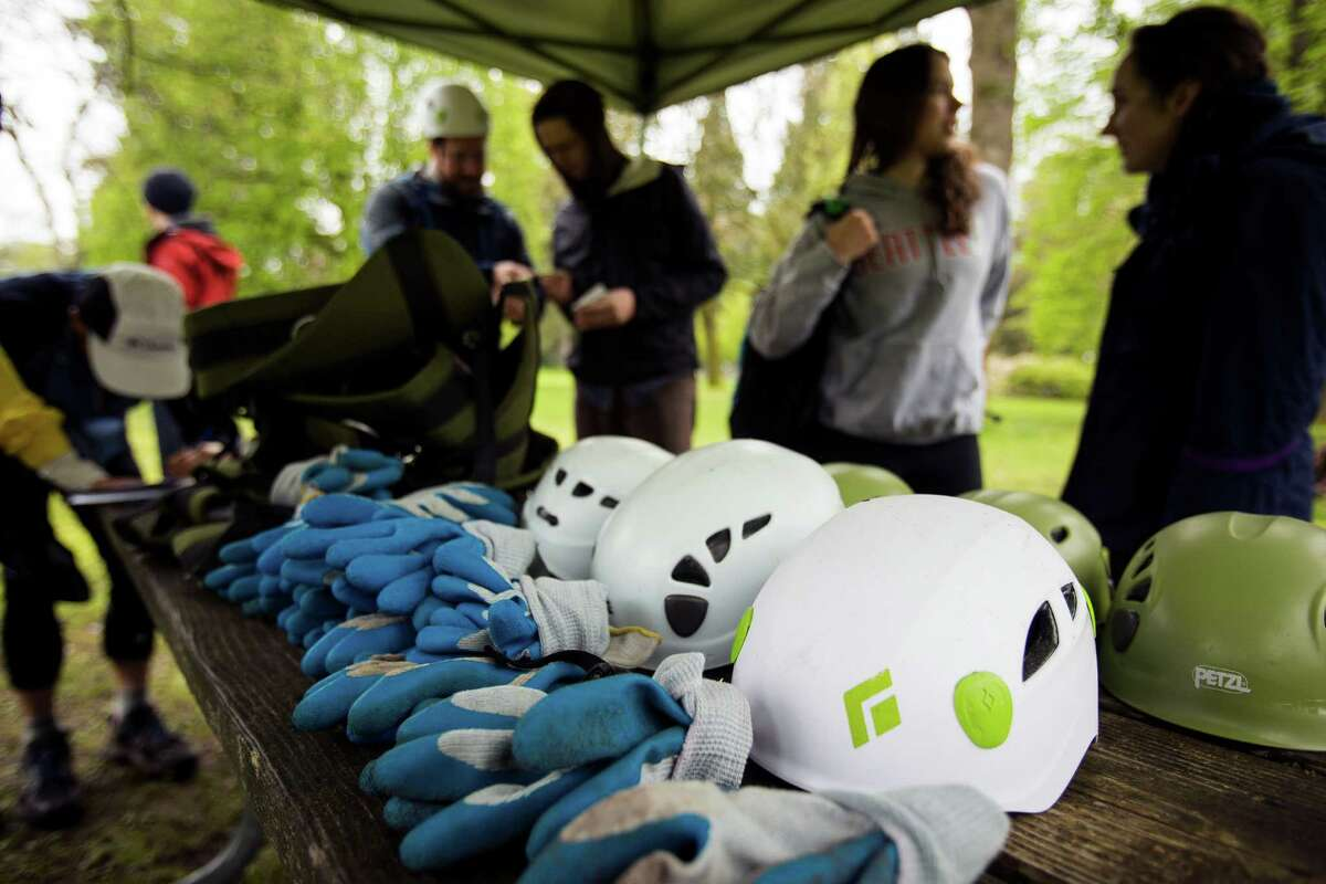 Attendees mingle near the gear table at a tree-climbing event put on by the Seattle-local, eco-adventuring Canopy Climbers in honor of Earth Day on Sunday at Volunteer Park in Seattle. Attendees took turns ascending a 110-foot red oak named
