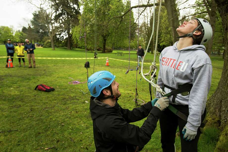 "Dave Bayard, center, helps unstrap Ellyn Rivers, right, following her ascent and descent at a tree-climbing event put on by the Seattle-local, eco-adventuring Canopy Climbers in honor of Earth Day on Sunday at Volunteer Park in Seattle. Attendees took turns ascending a 110-foot red oak named ""Her Majesty."" Photo: JORDAN STEAD, SEATTLEPI.COM / SEATTLEPI.COM"