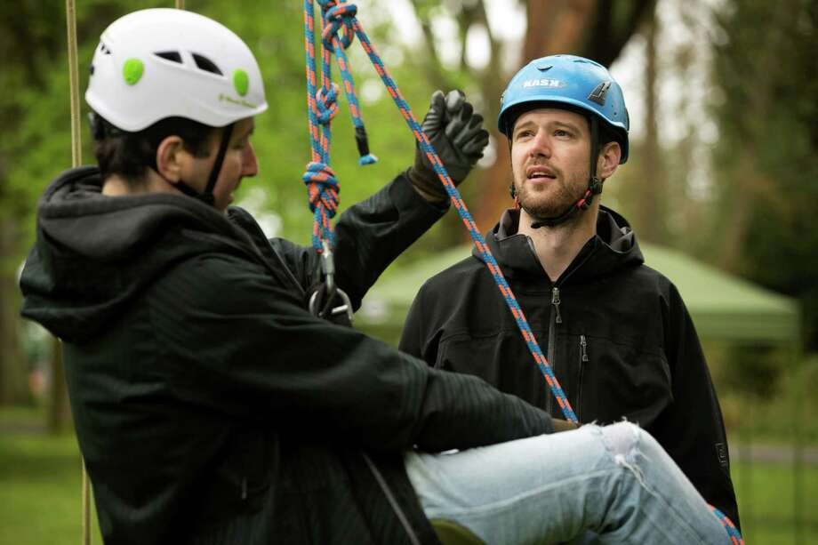 "Dave Bayard, right, gives technical advice to Dave Greenbaum, left, at a tree-climbing event put on by the Seattle-local, eco-adventuring Canopy Climbers in honor of Earth Day on Sunday at Volunteer Park in Seattle. Attendees took turns ascending a 110-foot red oak named ""Her Majesty."" Photo: JORDAN STEAD, SEATTLEPI.COM / SEATTLEPI.COM"