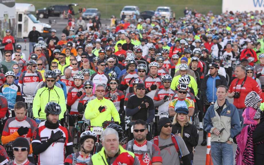 Cyclists listen to the National Anthem before the start of the 29th Annual BP MS 150 trek from Houston to Austin, Saturday, April 20, 2013 at Rhodes Stadium in Katy, Texas. Approximately 12,000 cyclists will embark on the two-day, 180-mile journey to drive awareness for a cure for multiple sclerosis. (AP Photo/The Courier, Alan Warren)