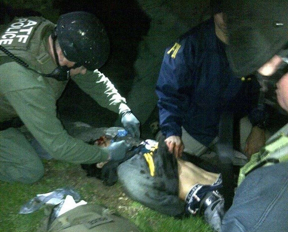 In this Friday, April 19, 2013 file photo obtained by The Associated Press and authenticated by a member of the Bureau of Alcohol, Tobacco, Firearms and Explosives, ATF and FBI agents check suspect Dzhokhar Tsarnaev for explosives and also give him medical attention after he was apprehended in Watertown, Mass., at the end of a tense day that began with his older brother, Tamerlan, dying in a getaway attempt. Tsarnaev lay hospitalized in serious condition under heavy guard Saturday as investigators continue piecing together the who and why of the two brothers involved in the deadly Boston Marathon bombings. Since Monday, Boston has experienced five days of fear, beginning with the marathon bombing attack, an intense manhunt and much uncertainty ending in the death of one suspect and the capture of the other. Photo: File