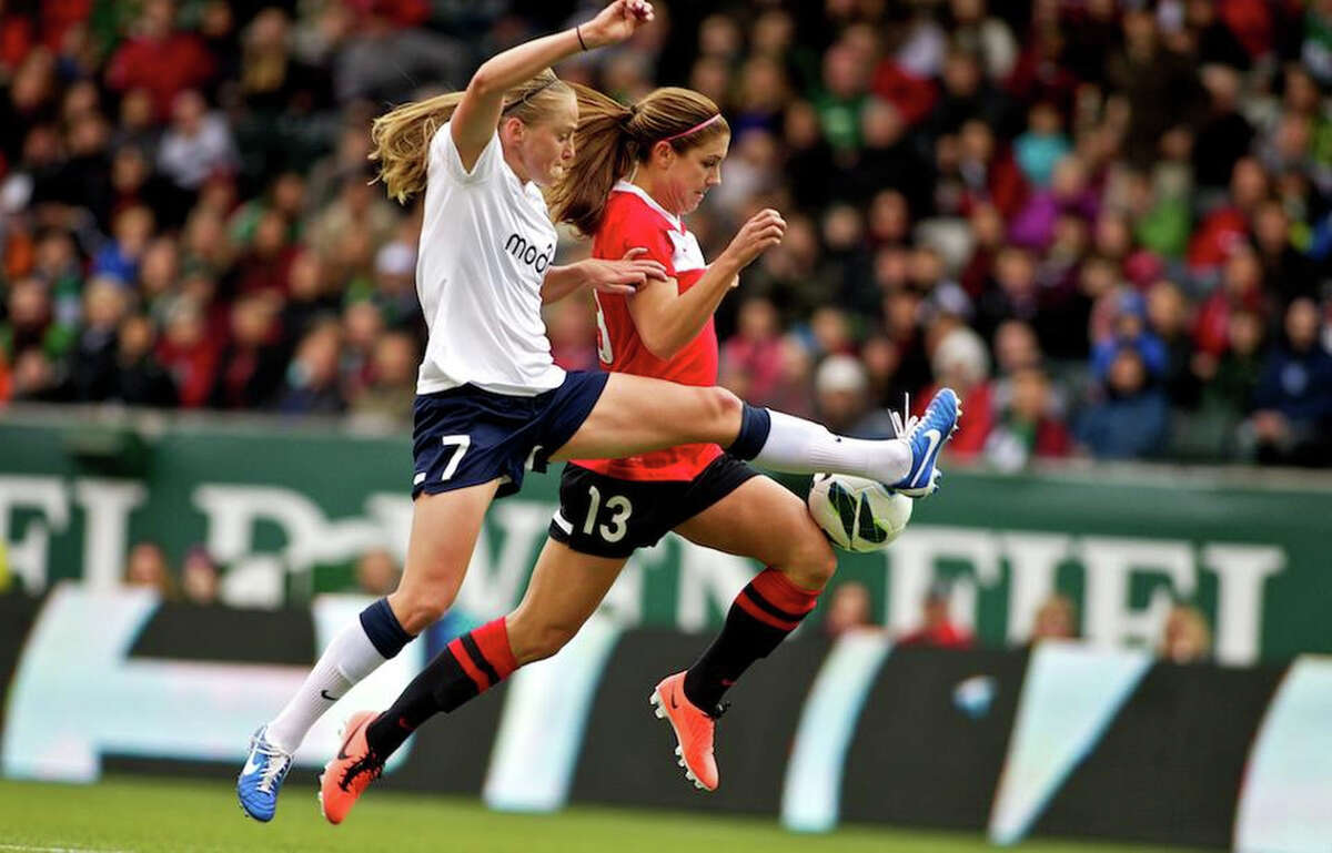 Seattle Reign player Elli Reed tries to take the ball from Portland Thorns forward Alex Morgan (13) as she attempts a shot on goal at JELD-WEN Field on April 21, 2013. Alex Morgan and Marian Dougherty each scored a goal to lead the Portland Thorns to a 2-1 victory over the Reign. The match drew 16,479 fans - a record for the National Women's Soccer League in its debut season.