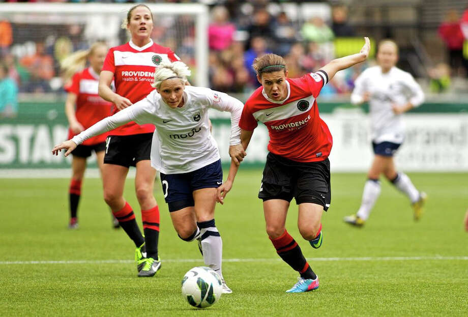 Seattle Reign player Jess Fishlock races to the ball against Portland Thorns forward Christine Sinclair (12) at JELD-WEN Field on April 21, 2013. Photo: Craig Mitchelldyer, Portland Thorns FC / Portland Thorns FC
