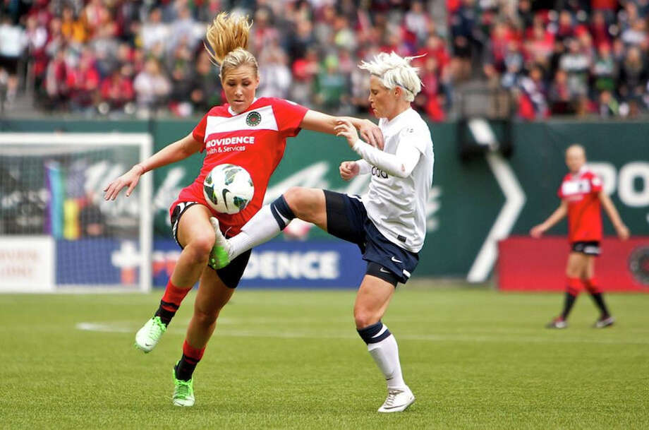 Portland Thorns midfielder Allie Long (10) is fouled by Seattle Reign player Jess Fishlock at JELD-WEN Field on April 21, 2013. Photo: Craig Mitchelldyer, Portland Thorns FC / Portland Thorns FC