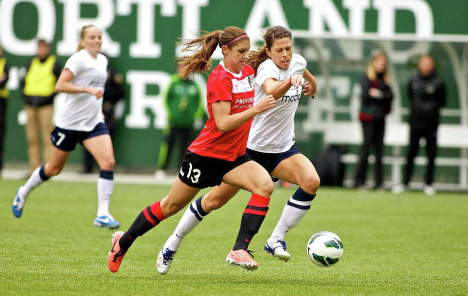 Seattle Reign player Emily Zurrer and Portland Thorns forward Alex Morgan (13) race for the ball at JELD-WEN Field on April 21, 2013. Photo: Craig Mitchelldyer, Portland Thorns FC / Portland Thorns FC