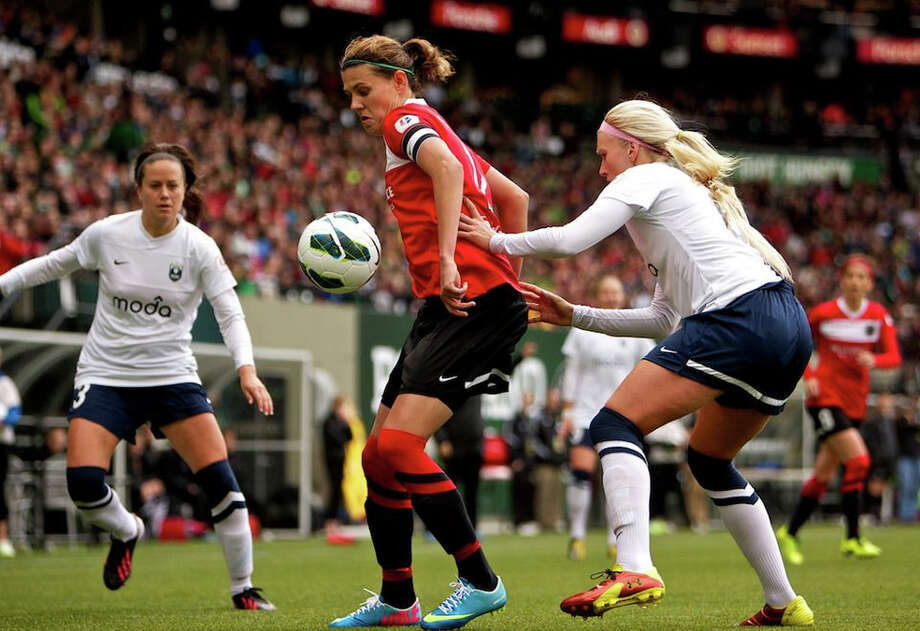 Portland Thorns forward Christine Sinclair (12) controls the ball against Seattle Reign player Kaylyn Kyle, right, at JELD-WEN Field on April 21, 2013. Photo: Craig Mitchelldyer, Portland Thorns FC / Portland Thorns FC