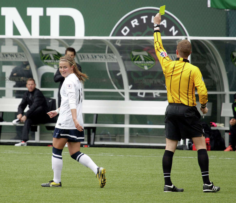 Seattle Reign midfielder Christine Nairn, left, looks back as she receives a yellow card during the first half. Photo: Don Ryan, AP / AP