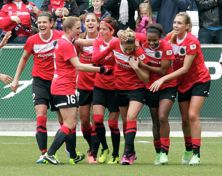 The Portland Thorns celebrate after Kathryn Williamson, third from right, scores during the first half of a National Women's Soccer League soccer game against the Seattle Reign. Photo: Don Ryan, AP / AP