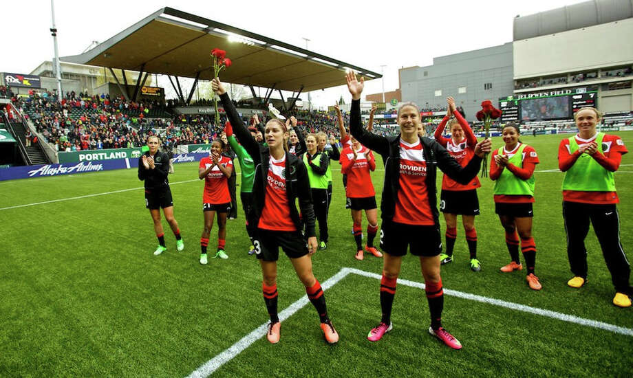 The Thorns hold up roses after winning 2-1 at JELD-WEN Field on April 21, 2013. Alex Morgan and Marian Dougherty each scored a goal to lead the Portland