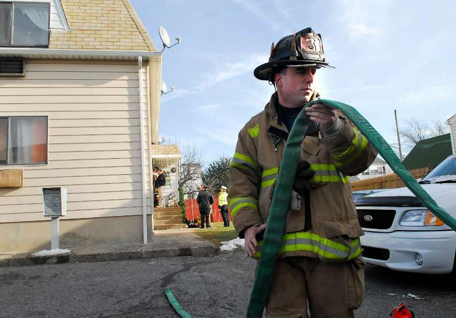 Stamford firefighter, Chris Lioti, rolls up a hose during the aftermath of a fire at a 2 story wood-framed house on Victory Street, Stamford, early Thursday afternoon, Jan. 7th, 2009.  Fire official on the scene said no one was injured. Photo: Bob Luckey / Stamford Advocate