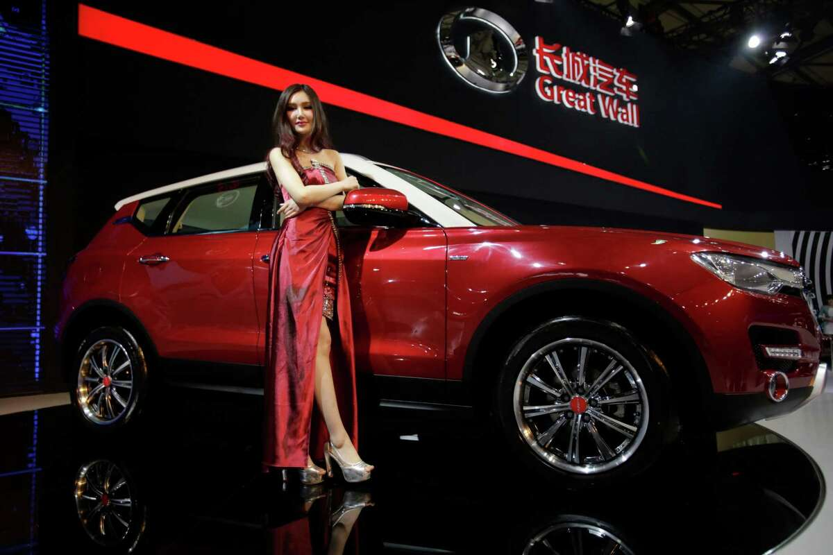 A model poses with Great Wall H7 SUV at the Shanghai International Automobile Industry Exhibition (AUTO Shanghai) media day in Shanghai, China Saturday, April 20, 2013. China's most successful SUV producer, Great Wall Motor Co., is coming out with a model that offers the room of a luxury SUV at a mid-range price. The Chinese brand, which exports SUVs to 80 countries, unveiled the H7 and its sister sport model, the H6, on Saturday ahead of the Shanghai auto show. Great Wall is one exception to the trend of independent Chinese brands struggling against foreign competition in their home market.