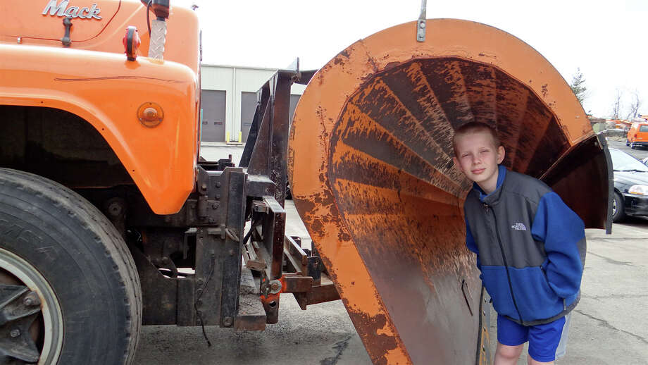 Ben Ratner, 10, of Fairfield, isurrounded by the scoop of a Fairfield Department of Public Works plow during a tour of the department's headquarters Saturday morning.  FAIRFIELD CITIZEN, CT 4/20/13 Photo: Mike Lauterborn / Fairfield Citizen contributed