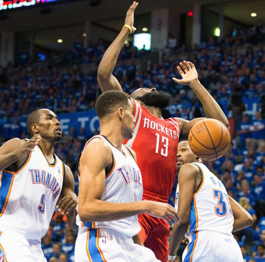 James Harden loses the ball on a drive to the basket as Oklahoma City center Kendrick Perkins (5), shooting guard Thabo Sefolosha (2), and small forward Kevin Durant (35) look on during the first half. Photo: Smiley N. Pool, Houston Chronicle
