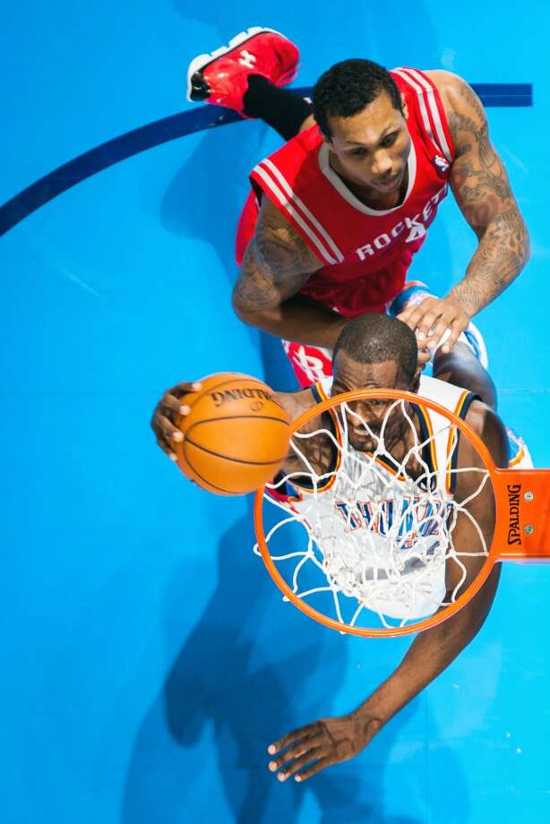 Thunder power forward Serge Ibaka dunks the ball past Rockets power forward Greg Smith. Photo: Smiley N. Pool, Houston Chronicle