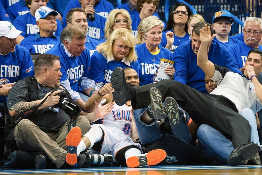 Thunder point guard Russell Westbrook and referee Tommy Nunez Jr. tumble into the photographers. Photo: Smiley N. Pool, Houston Chronicle