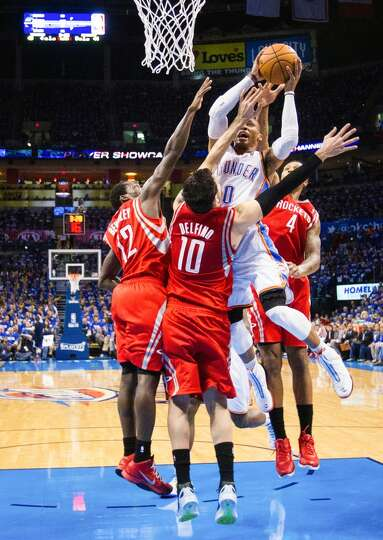 Thunder point guard Russell Westbrook (0) attracts a triple team from the Rockets Patrick Beverley (