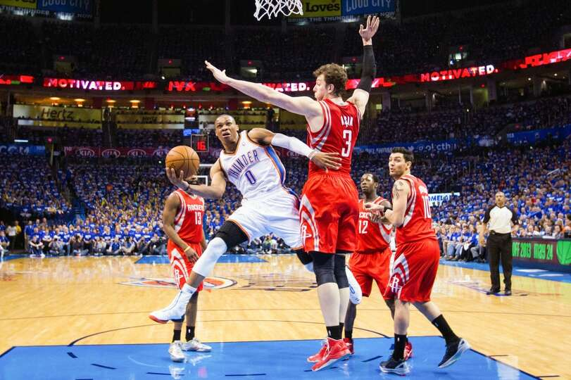 Thunder point guard Russell Westbrook (0) drives to the basket past Rockets center Omer Asik.