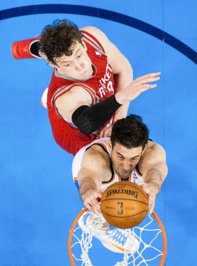 City Thunder power forward Nick Collison dunks the ball past Rockets center Omer Asik. Photo: Smiley N. Pool, Houston Chronicle