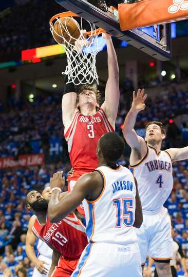Rockets center Omer Asik (3) dunks the ball as Thunder point guard Reggie Jackson (15) and power for