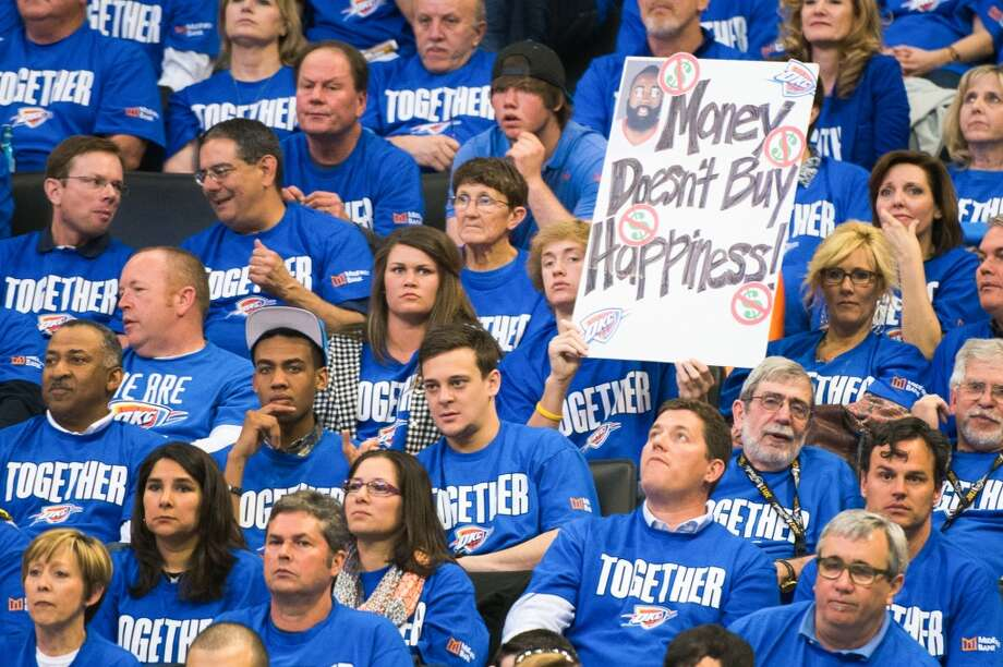 A Thunder fan holds a sign referencing Rockets guard James Harden, who played in Oklahoma City last season. Photo: Smiley N. Pool, Houston Chronicle