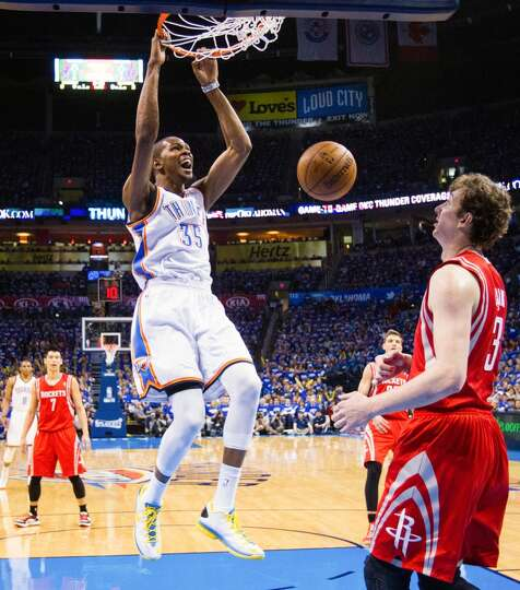Thunder small forward Kevin Durant dunks the ball as Houston Rockets center Omer Asik can only watch