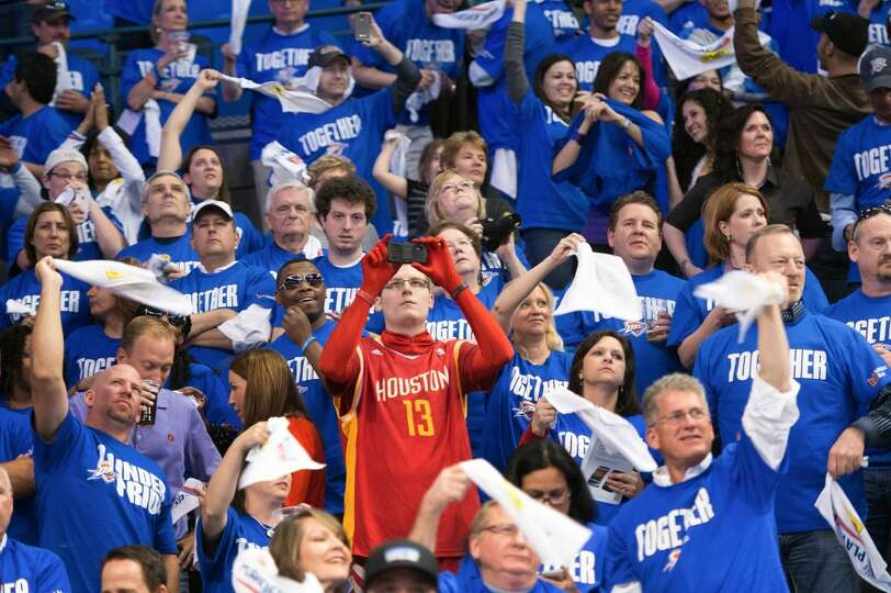 A lone Rockets fan is surrounded by a sea of blue clad Thunder fans during the first half.