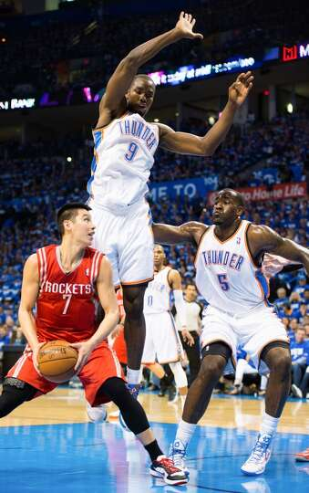 Rockets point guard Jeremy Lin (7) is defended by Thunder power forward Serge Ibaka (9) and center K