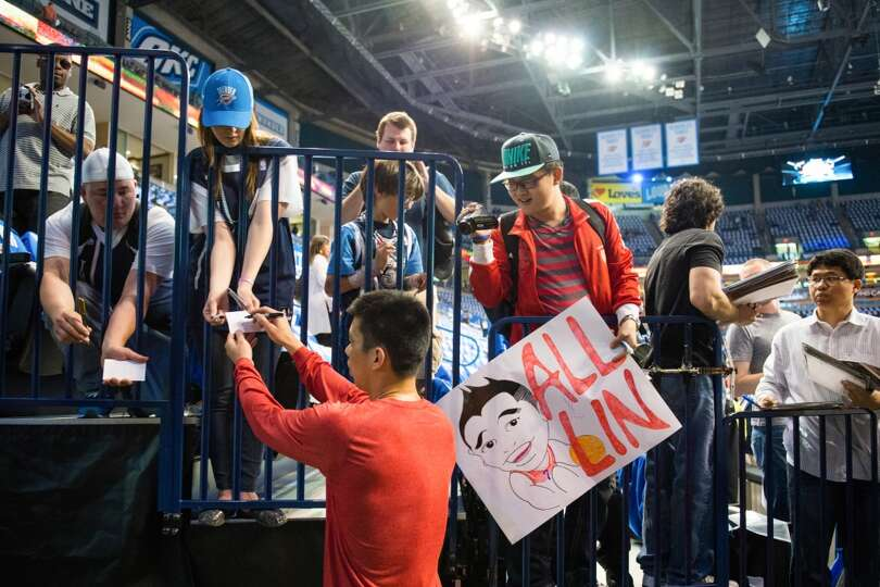Rockets point guard Jeremy Lin signs autographs for fans before the game.