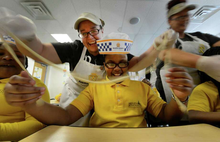 Dina Locklear, from Auntie Anne's Pretzels, works with third-grade student Semiya Wilson at Henry Johnson Charter Friday, April 19, 2013, in Albany, N.Y. The party was designed to instill teamwork and perseverance in the students. (Skip Dickstein/Times Union) Photo: SKIP DICKSTEIN / 00022047A