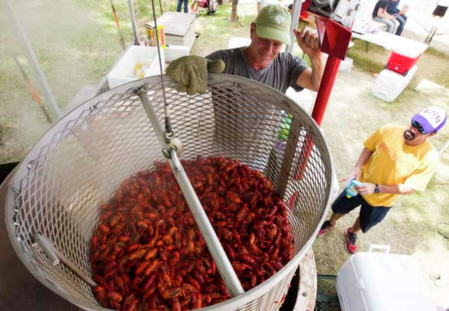 Jay Davidson with the Cajun Kookers team takes 90 pounds of crawfish out of the cooker. Photo: J. Patric Schneider, For The Chronicle / © 2013 Houston Chronicle