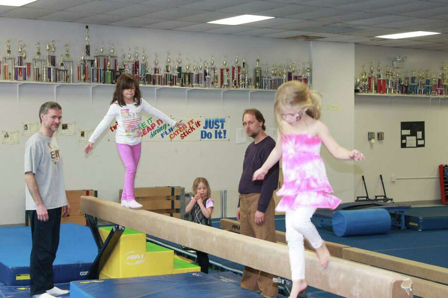 Giving the balance beam a go, with the Gymnastic teams\' trophies as a backdrop