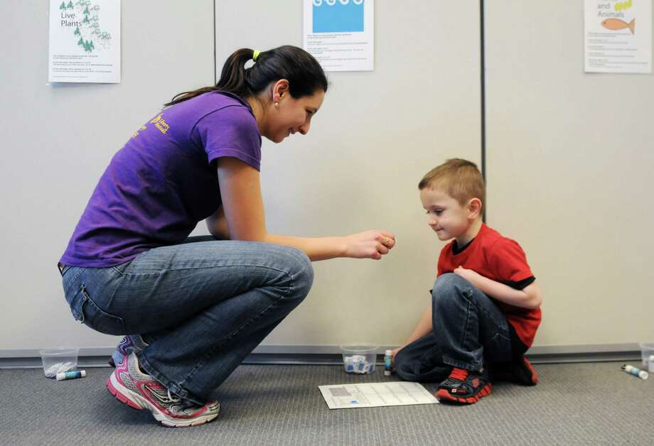 University at Albany grad student, Hannah Attard of Buffalo, left, guides Samuel Marshall, 6, right, of Loudonville though an interactive traveling nitrogen game Sunday, April 21, 2013, during Family Earth Day events at the University at Albany in Albany, N.Y. The afternoon event aimed to raise community awareness about recycling, the atmosphere and environmental science research. (Will Waldron/Times Union) Photo: Will Waldron, Albany Times Union / 10022014A
