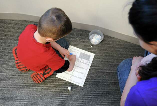 Samuel Marshall, 6, of Loudonville, left, adds a sticker to his University at Albany Family Earth Day passport, while being assisted though an interactive traveling nitrogen game by grad student, Hannah Attard of Buffalo, right, Sunday, April 21, 2013, at the University at Albany in Albany, N.Y. The afternoon event aimed to raise community awareness about recycling, the atmosphere and environmental science research. (Will Waldron/Times Union) Photo: Will Waldron, Albany Times Union / 10022014A