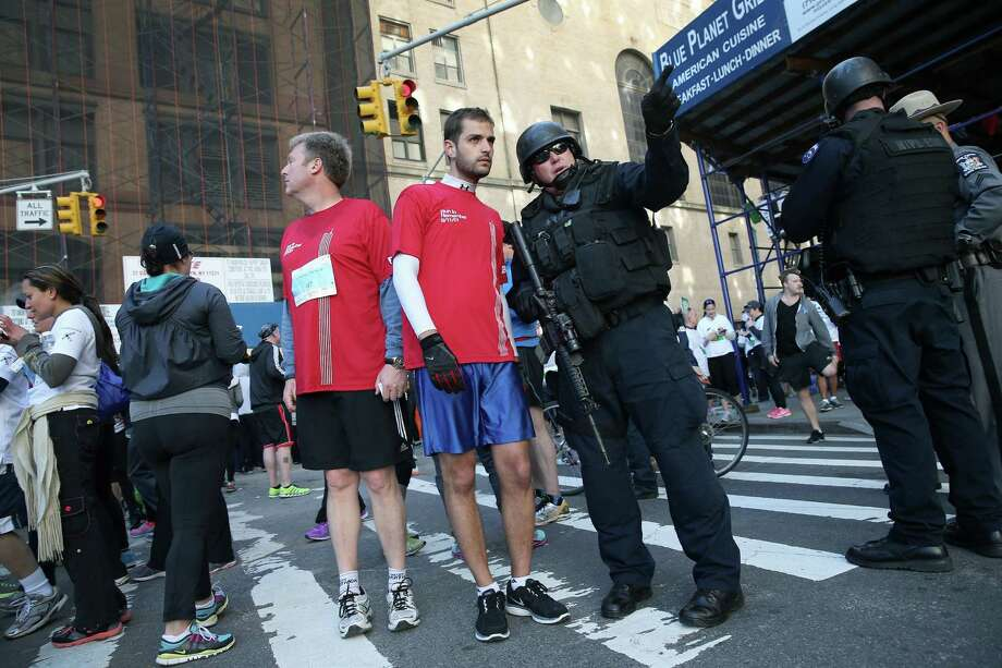 NEW YORK, NY - APRIL 21:  A heavily armed policeman directs a runner following the first 9/11 Memorial 5K Run/Walk on April 21, 2013 in New York City. Security was tight for the race, as has been the case in large scale events around the country since the Boston Marathon bombings. April 21 marks the anniversary that President Barack Obama signed into law legislation making 9/11 a day of service and volunteerism in memory of the victims of the 2001 attacks. Photo: John Moore, Getty Images / 2013 Getty Images