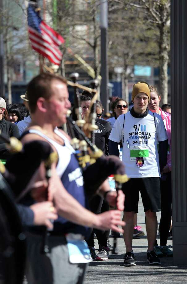 NEW YORK, NY - APRIL 21:  Runners watch a police bagpipe band play following the 9/11 Memorial 5K Run/Walk on April 21, 2013 in New York City. Security was tight for the race, as has been the case in large scale events around the country since the Boston Marathon bombings. April 21 marks the anniversary that President Barack Obama signed into law legislation making 9/11 a day of service and volunteerism in memory of the victims of the 2001 attacks. Photo: John Moore, Getty Images / 2013 Getty Images