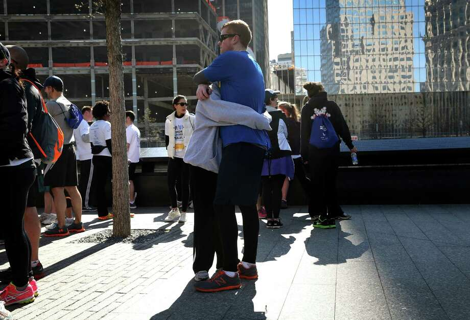 NEW YORK, NY - APRIL 21:  Runners embrace following the 9/11 Memorial 5K Run/Walk on April 21, 2013 in New York City. Security was tight for the race, as has been the case in large scale events around the country since the Boston Marathon bombings. April 21 marks the anniversary that President Barack Obama signed into law legislation making 9/11 a day of service and volunteerism in memory of the victims of the 2001 attacks. Photo: John Moore, Getty Images / 2013 Getty Images