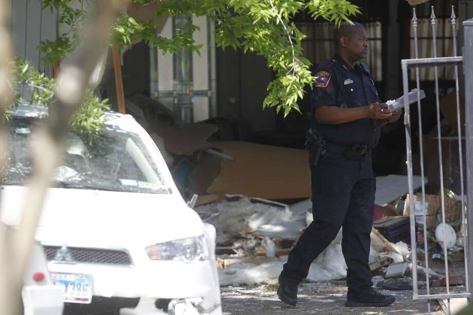 A police officer walks through the crash scene after a man drove into a home near 500 N. Wilcrest Dr. at Taylorcrest.