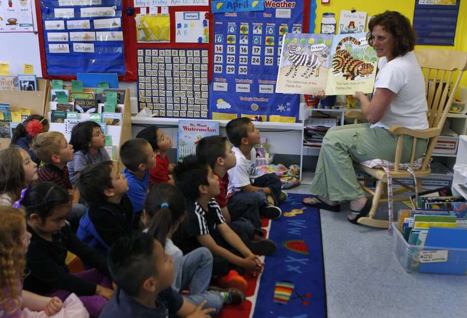 Jennifer Overbey reads a book to her kindergarten students at Clifford Elementary School in Redwood City, Calif. on Friday, April 12, 2013. Some homes in San Carlos that are within Clifford\'s region sell at a slightly lower value because the school\'s test scores are not quite as high as others in the area.