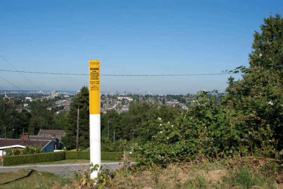 A pipeline marker in an urban area of Burnaby, British Columbia. Pipeline markers are part of the integrity program to ensure the community is aware of location. The marker contains information about who to call for safe digging process and emergency response. Photo: Trans Mountain