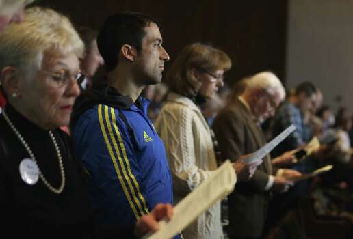 Wearing his Boston Marathon runner's jacket, David Delmar, 28, second from left, a member of Trinity Episcopal Church in Boston, attends a service at Temple Israel, which allowed the Trinity congregation to hold their service, Sunday, April 21, 2013, in Boston. Trinity is within the blocked-off area near the finish line of the Boston Marathon, where earlier in the week two bombs exploded. Delmar, who finished the marathon about 30 minutes before the explosions, was running his first marathon as part of charity to Trinity. Photo: Julio Cortez
