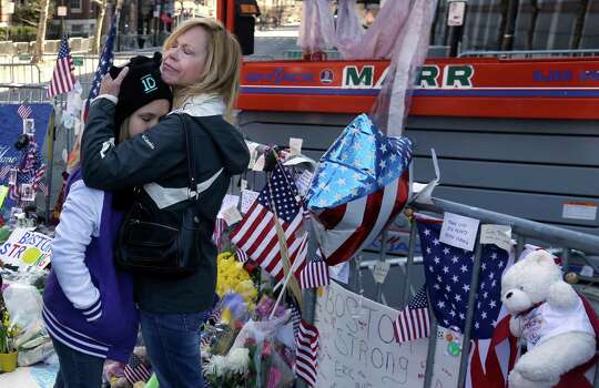 Holly Holland, right, of St. Louis, hugs her daughter Katie Holland while visiting a makeshift memorial in Boston, Monday, April 22, 2013. The memorial sits on Boylston Street, not far from where two bombs exploded near the finish line of the Boston Marathon, on Monday, April 15. Photo: Steven Senne