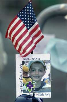 A photograph of bombing victim Martin Richard, 8, is attached to a barricade in Boston, Monday, April 22, 2013, at a makeshift memorial on the street not far from where two bombs exploded near the finish line of the Boston Marathon, Monday, April 15, 2013. Richard was among three people killed in the bombings at the finish line of the race last Monday. Photo: Steven Senne